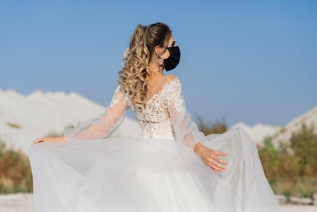 코로나 바이러스 covid-19 격리 기간에 의료 마스크가 달린 웨딩 드레스의 신부.