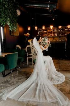 Невеста в свадебных платьях на модном кресле в кафе.