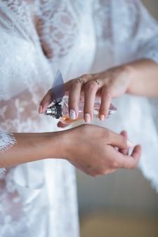 彼女の手首に香水を適用する白いブドワールシャツの花嫁