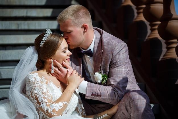 白いドレスを着た花嫁と衣装を着た新郎が階段に抱きしめます