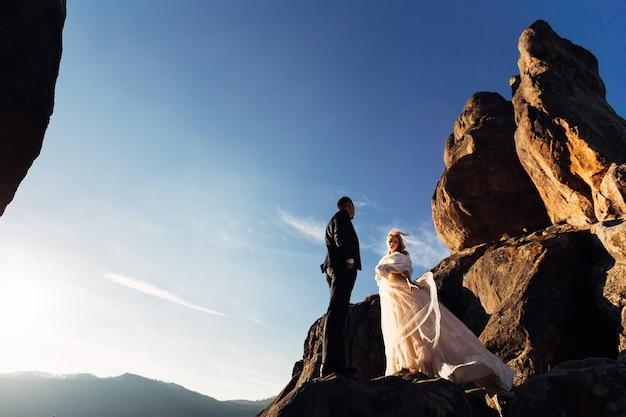 白いドレスを着た花嫁と崖や山々を背景に風に吹かれて髪を吹く