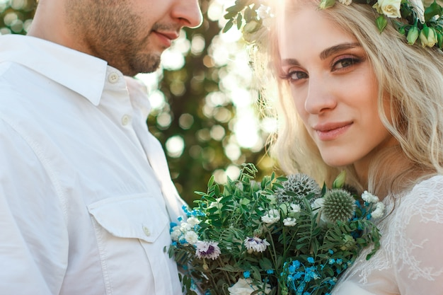 夏の日の白いドレスと花輪と新郎の肖像画の花嫁素朴な屋外の結婚式のコンセプト