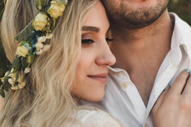 晴れた夏の日の白いドレスと花輪と新郎の肖像画の花嫁素朴な屋外の結婚式