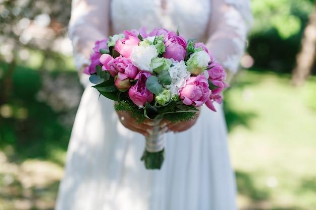 白いドレスの花嫁はピンクの花の結婚式の花束を保持している女性の手でスタイリッシュな花束をクローズアップ