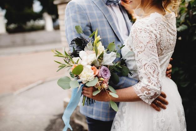 白いドレスの花嫁は、ウェディングブーケを保持しています。新郎は花嫁を抱きしめます。