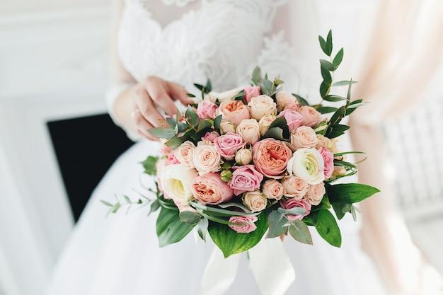 白いドレスの花嫁は、ウェディングブーケを保持しています。