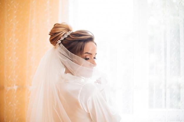 Невеста в белом платье позирует во время подготовки к свадебной церемонии