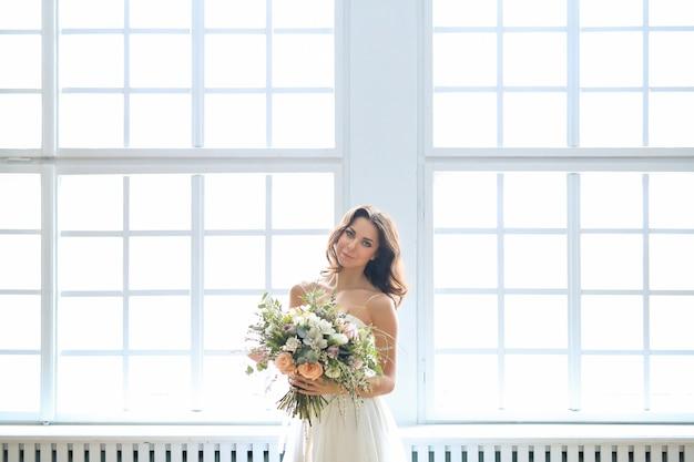 Невеста в белом платье держит букет цветов