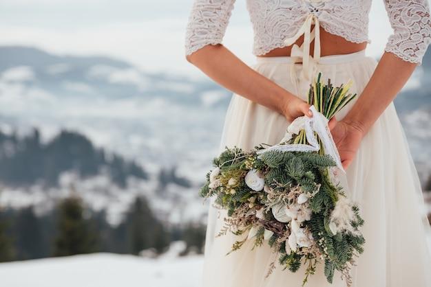 Невеста в белом свадебном платье держит в руках букет ярких цветов