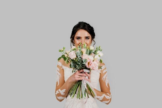 Невеста в белом свадебном платье выглядит изысканным букетом и улыбается