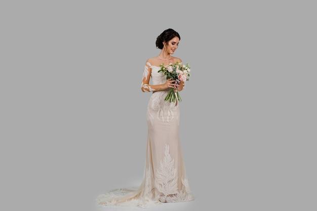 Невеста в белом свадебном платье с букетом в студии на белой глухой стене справа.