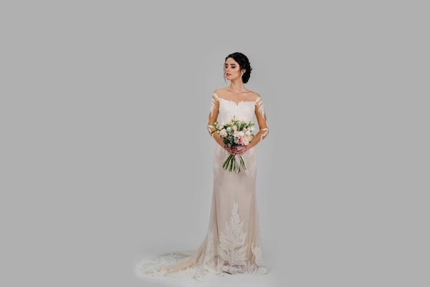 Невеста в белом свадебном платье с букетом смотрит влево в студии на белой глухой стене.