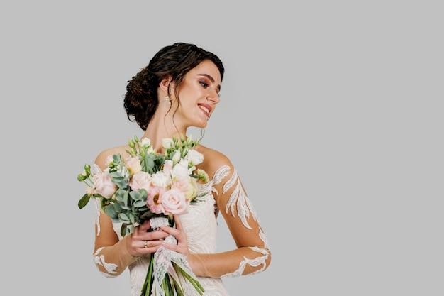 Невеста в белом свадебном платье с букетом смотрит вправо