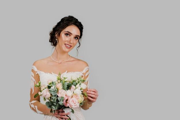 Невеста в белом свадебном платье с букетом