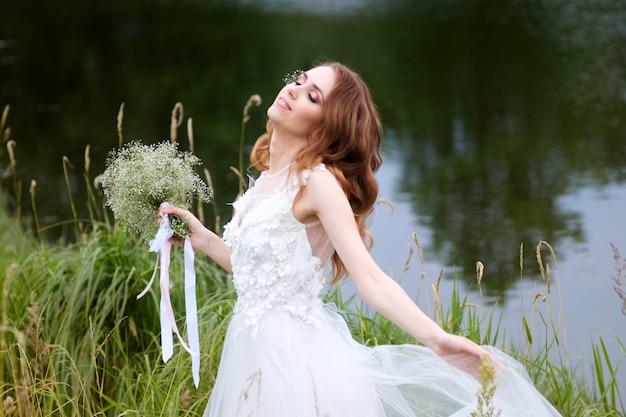 目を閉じて白いウェディングドレスの花嫁は湖の近くを歩くのを楽しんでいます