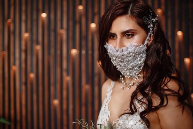 彼女の顔に手作りの結婚式の抗ウイルスマスクで花嫁。
