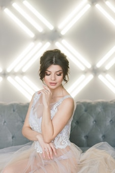 The bride is a european-looking brunette. single portrait. wedding makeup and hairstyle. morning of the bride. boudoir at the hotel.