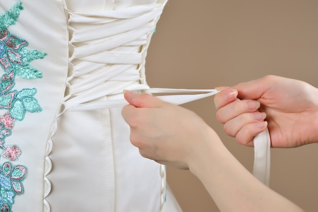 The bride is helped to lace up the corset top view