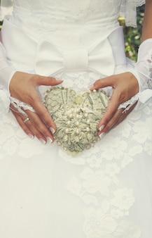 Невеста держит старинное сердце, украшенное жемчугом