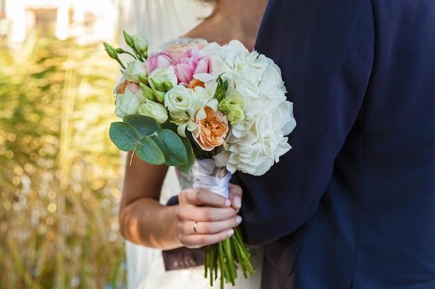 花嫁は美しい明るいウェディングブーケを保持しています