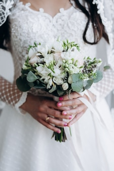 Bride is holding beautiful wedding bouquet of white flowers and eucalyptus
