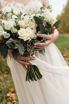 The bride is holding a beautiful white wedding bouquet. close up. autumn.