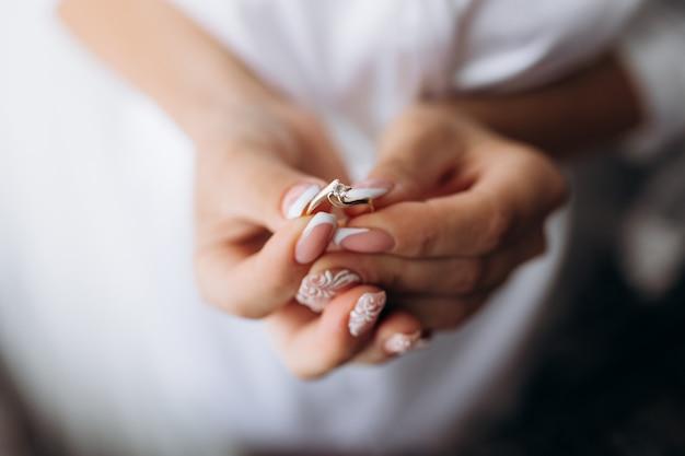 신부는 그녀의 손에 부드러운 약혼 반지를 들고있다