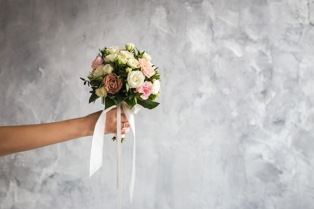 The bride is holding a wedding bouquet on gray