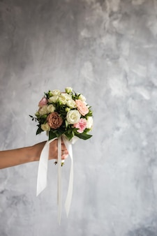 The bride is holding a wedding bouquet on a gray