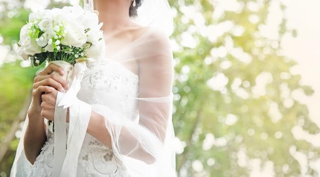 Невеста держит белый розовый букет в руке, теплый светлый тон Premium Фотографии