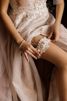 Bride is putting on her leg tender wedding garter, dressed in wedding dress with tattoo on the leg