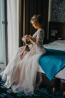 The bride is sitting on the bed in the hotel.