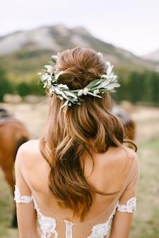 Невеста стоит спиной в красивом кружевном платье. голова невесты украшена венком.