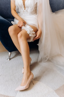 신부는 안락 의자에 앉아 그녀의 다리에 웨딩 양말을 착용