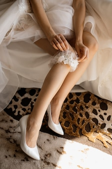 신부는 그녀의 다리에 웨딩 양말을 착용