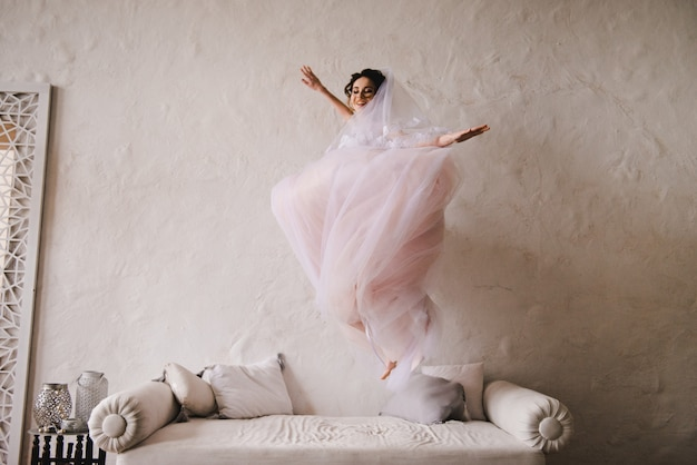 The bride jumps on the couch. the bride is gathering in the morning. stylish pink wedding dress.