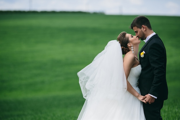 Bride kissing her husband's lips outdoors