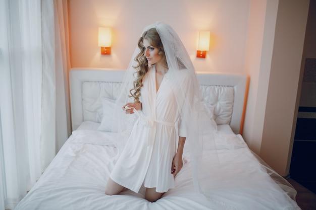 ベッドの上にひざまずい花嫁