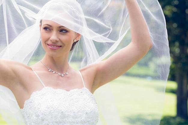Bride lifting her veil in garden