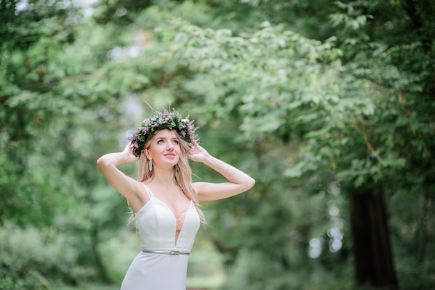 Bride in light white dress stands in wreath in the forest