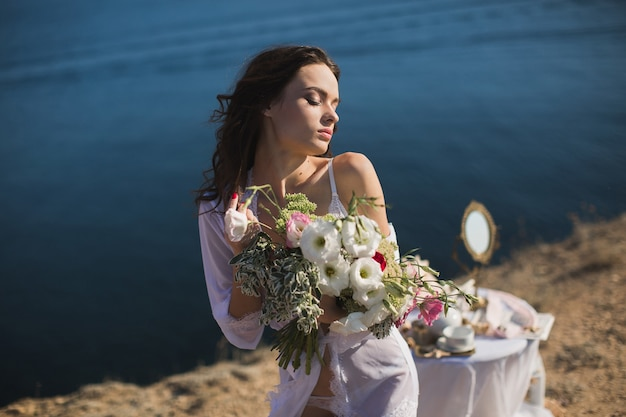 Bride in lingerie. holds the bridal bouquet . charges of the bride, bride's morning.