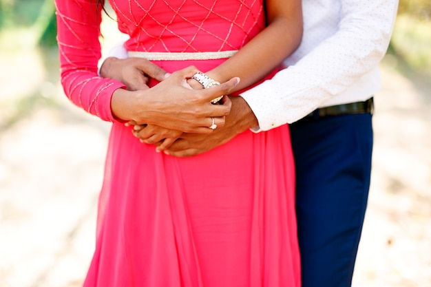 The bride in a long bright pink dress and the groom stand hugging tenderly the bride put her hands