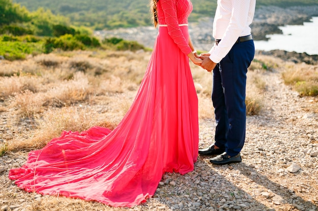 The bride in a long bright pink dress and the groom stand on a summer day in nature and tenderly