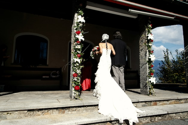 Bride in a long dress walks into the old chapel
