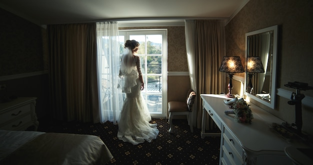 Bride looking through the window from the hotel room