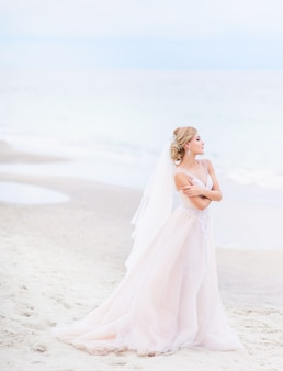 Bride looks gorgeous standing on the white sand before the sea