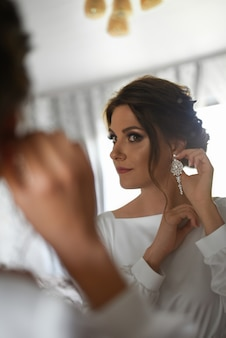 The bride looks in the mirror before the wedding in the morning