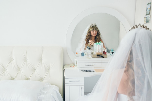 The bride looks in the mirror and uses perfume in the white room