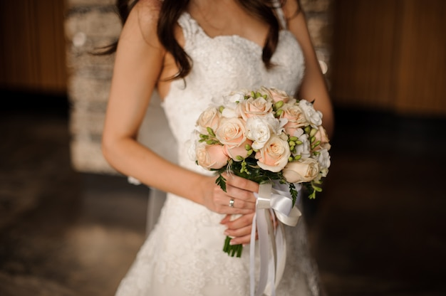Bride in a lovely white dress holding a wedding bouquet