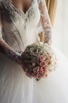 Bride in luxurious dress holds bouquet of white orchids and pink roses